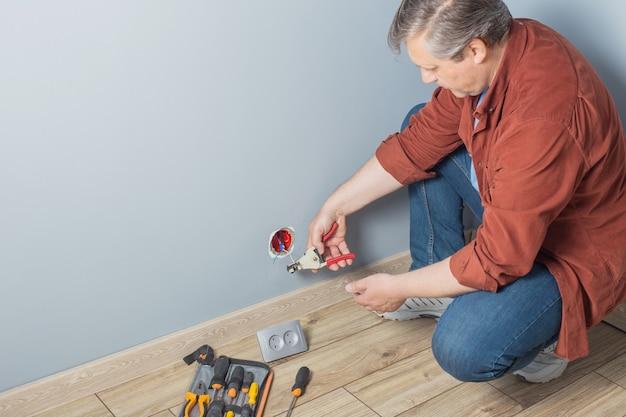 Man installeert een stopcontact op een grijze muur