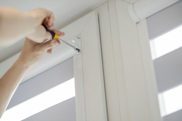 Man installeren cassette rolluiken op ramen