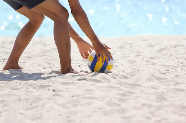 Man is gebogen pak de volleybal op zeezand