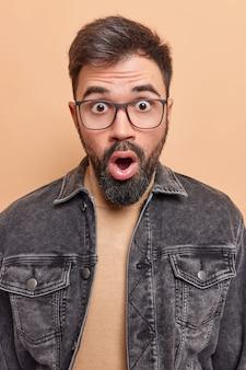 Man is getuige van rampspoed houdt mond wijd open herinnert zich iets ergs draagt bril hapt naar adem van verwondering poseert binnen zegt wow