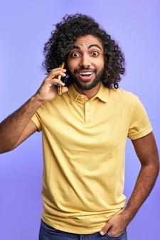 Man is verrast door gepraat, nieuws delen met vrienden tijdens het telefoneren, camera kijken met geopende mond, geïsoleerd