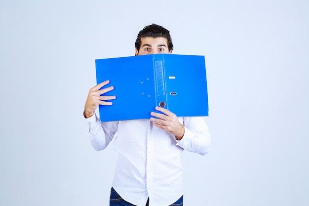 Man is verrast en verbergt zijn gezicht achter een blauwe map