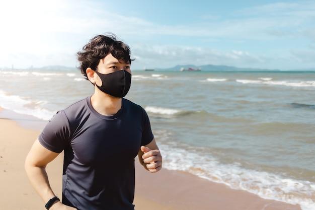 Man joggen op het strand met masker in de zomerochtend