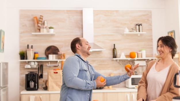 Man jongleert met sinaasappels voor vrouw terwijl hij een smakelijke en voedzame smoothie bereidt. gezonde, zorgeloze en vrolijke levensstijl, dieet eten en ontbijt bereiden op een gezellige zonnige ochtend