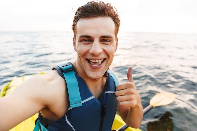 Man kajakken op meer zee in boot selfie maken met de camera.