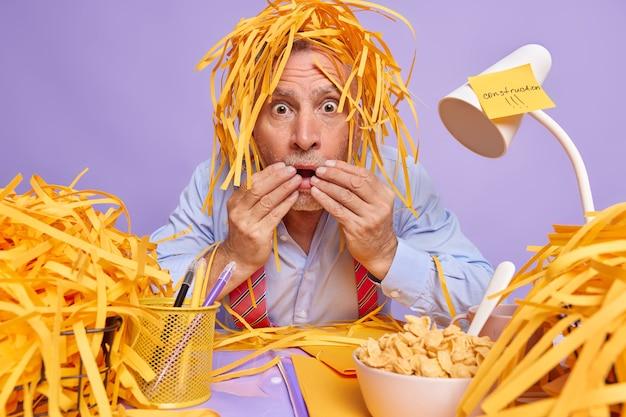 Man kantoormedewerker staart stomverbaasd heeft stapel gesneden papier op hoofd heeft bange blik poseert op rommelig bureaublad met kom ontbijtgranen mappen stickers rond