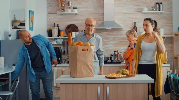 Man keert terug van de markt met fruit en brood. jong stel komt van winkelen en brengt een papieren zak met boodschappen, vers voedsel, van de supermarkt bij de ouders thuis om een familiediner te bereiden