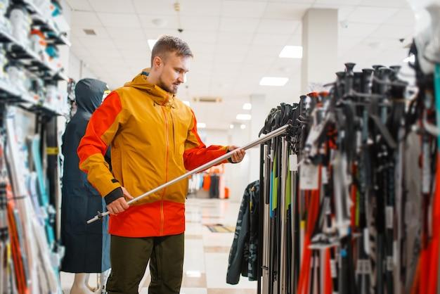 Man kiezen skistokken, winkelen in sportwinkel.