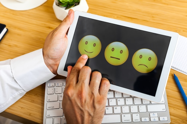 Man kiezen van zijn mening met smileygezichten op touchscreen