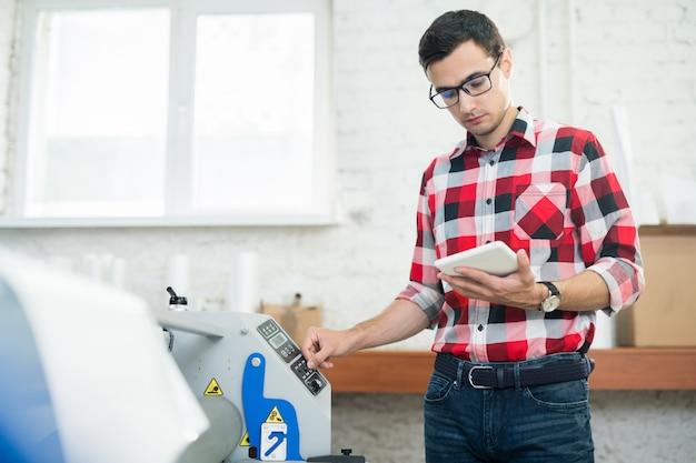 Man kijken naar tablet en met behulp van drukmachine