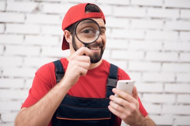 Man kijkt door loupe fixes smartphone.