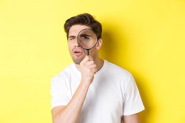 Man kijkt door vergrootglas met een serieuze en doordachte blik, zoekt of onderzoekt, staande over gele achtergrond.