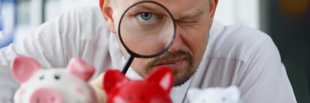 Man kijkt door vergrootglas naar spaarvarken