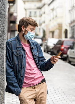 Man kijkt door zijn telefoon terwijl hij buiten een medisch masker draagt