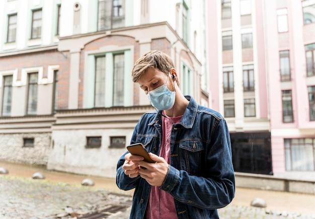 Man kijkt door zijn telefoon terwijl hij een medisch masker met kopie ruimte draagt