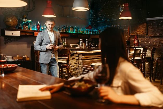 Man kijkt liefdevol op vrouw aan houten toog, romantisch diner met pasta en rode wijn. liefhebbers van vrije tijd in pub, man en vrouw ontspannen samen in nachtclub