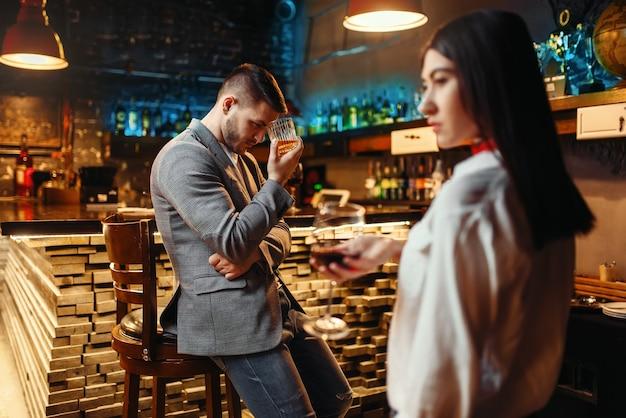 Man kijkt liefdevol op vrouw aan houten toog