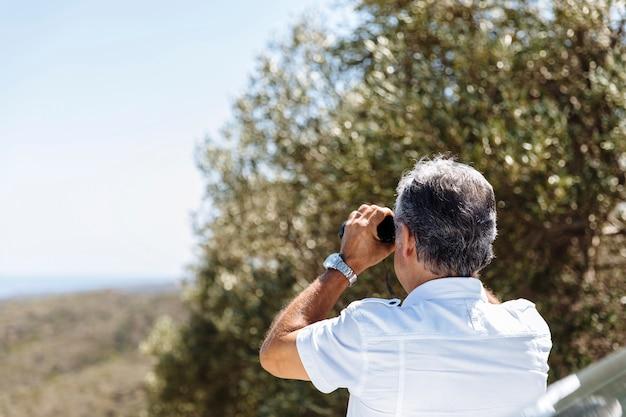 Man kijkt met een verrekijker
