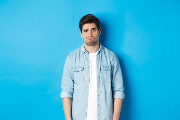 Man kijkt met twijfel naar de camera, fronst en mokt, voelt zich ergens ongemakkelijk over, staat tegen een blauwe achtergrond