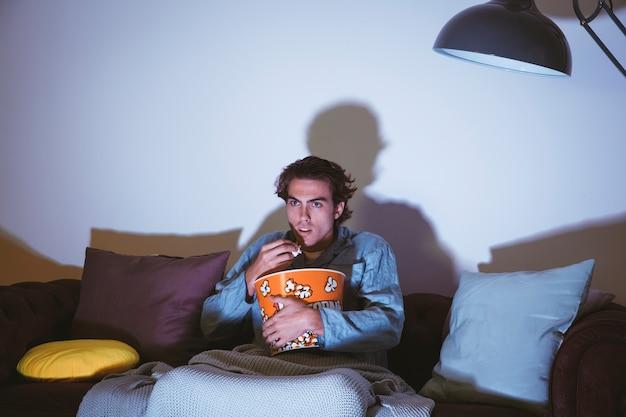 Man kijkt naar een film en eet popcorn