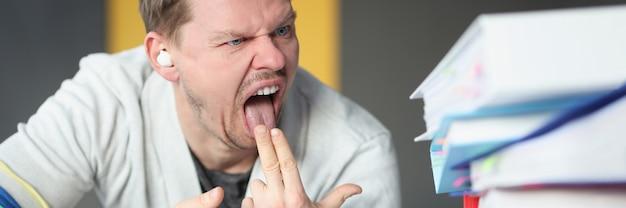 Man kijkt naar mappen met documenten en steekt twee vingers in zijn mond afkeer van werken