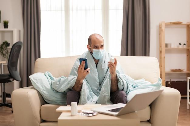 Man kijkt naar pillenfles tijdens een videogesprek op smartphone met arts.