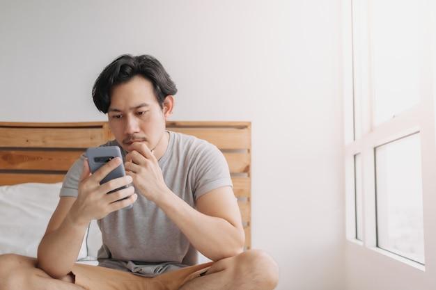 Man kijkt naar smartphone met een serieus gezicht