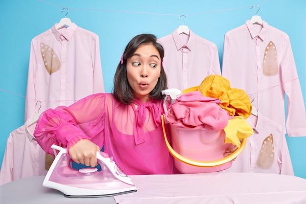Man kijkt naar stapel wasgoed in emmer gaat strijken bezig met huishoudelijke klusjes draagt roze blouse poses op blauw