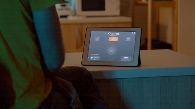 Man kijkt naar tablet in huis met automatiseringsverlichtingssysteem, zittend in de keuken en schakelt lampen in met spraakopdracht