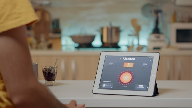 Man kijkt naar tablet met draadloze verlichtingsautomatiseringssoftware geplaatst op keukenbureau, huis met slim systeem, lichten aan. digitale tablet met high-tech app die de elektriciteitsefficiëntie regelt