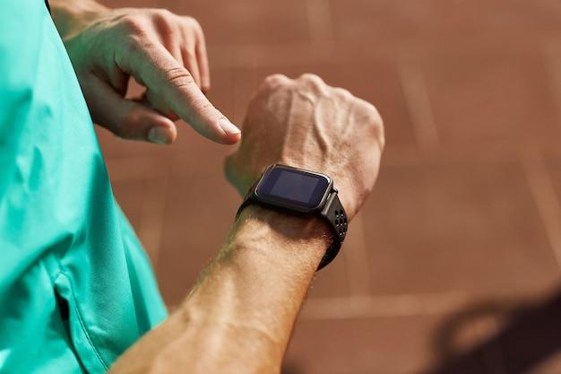 Man kijkt naar zijn smartwatch terwijl hij buiten traint close-up van man met zijn slimme horloge-app