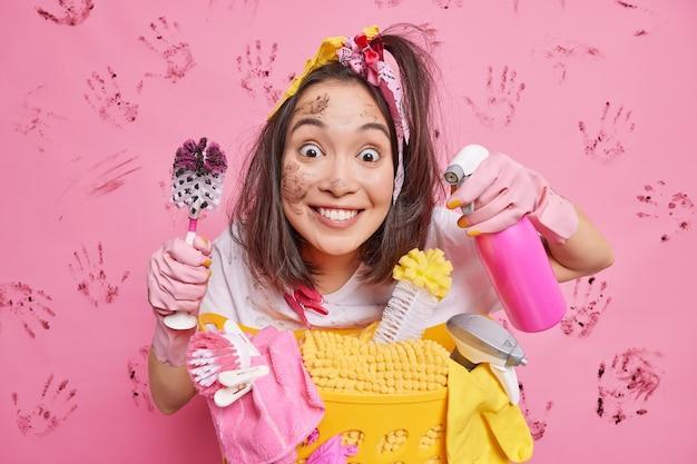 Man kijkt nauwgezet glimlacht positief poseert in de buurt van mand met schoonmaakbenodigdheden houdt vuile toiletborstel en dispenserfles geïsoleerd op roze