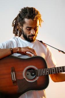 Man kijkt neer op zijn gitaar