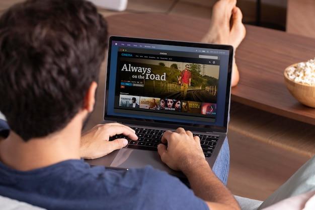 Man kijkt netflix op zijn laptop