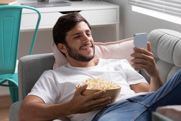 Man kijkt netflix op zijn telefoon