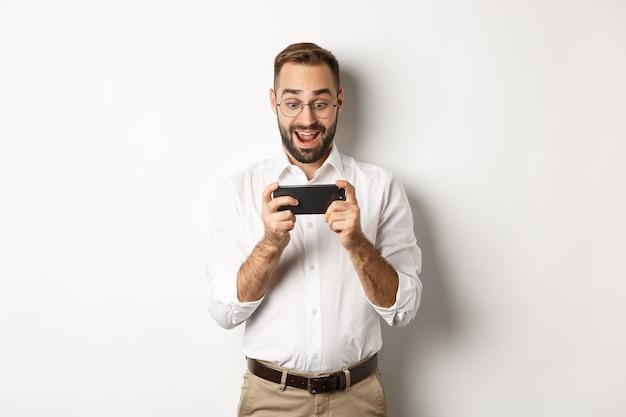 Man kijkt opgewonden en verbaasd naar mobiele telefoon, smartphone horizontaal te houden, staande.