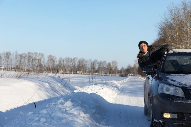 Man kijkt uit het autoraam naar de besneeuwde weg en glimlacht