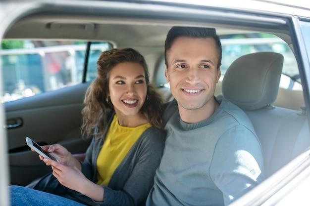 Man kijkt uit het raam en de vrouw in de auto