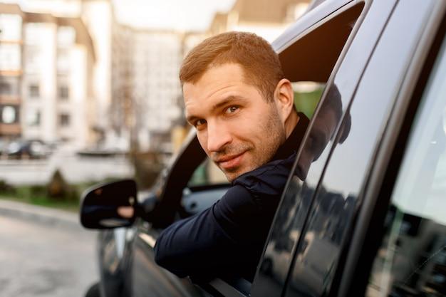 Man kijkt uit zijn auto en kijkt terug. de chauffeur bevindt zich in een woonwijk van de stad