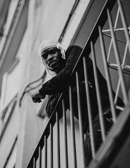 Man kijkt vanaf zijn balkon naar beneden tijdens sociaal isolement als gevolg van de covid-19-pandemie in groot-brittannië.