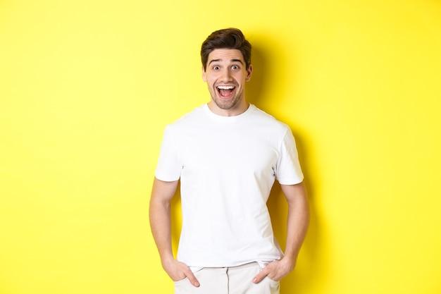 Man kijkt verbaasd, glimlachend verbaasd en kijkt naar aankondiging, staande in de buurt van kopie ruimte, gele achtergrond.