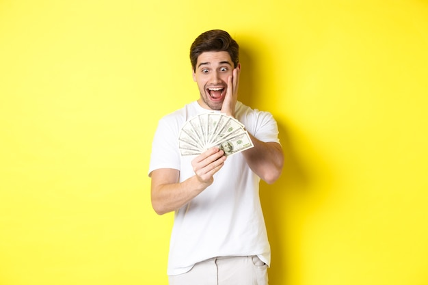 Man kijkt verbaasd naar geld, het winnen van een geldprijs, staande tegen een gele achtergrond.
