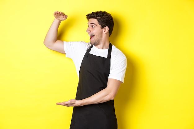 Man kijkt verbaasd naar iets groots, staande in zwarte schort tegen gele achtergrond.
