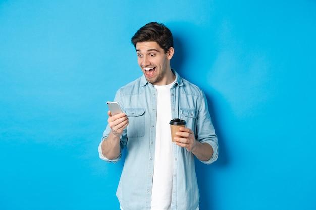 Man kijkt verbaasd naar smartphone, drinkt koffie, staat verbaasd over blauwe achtergrond