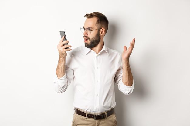 Man kijkt verward naar mobiele telefoon na gesprek, staande verbaasd kopieer de ruimte