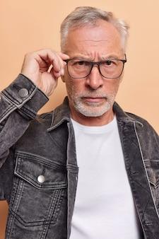 Man kijkt vol vertrouwen naar de camera houdt de hand op de rand van een bril die zelfverzekerd is, heeft een strikte uitdrukking en draagt styliskleren geïsoleerd op beige.