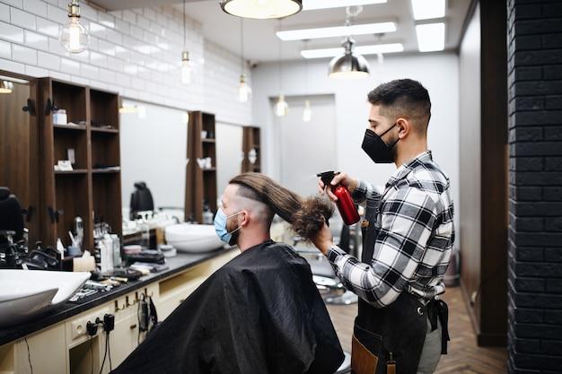 Man klant op bezoek bij kapper en haarstylist in kapperszaak, coronavirus en nieuw normaal concept.