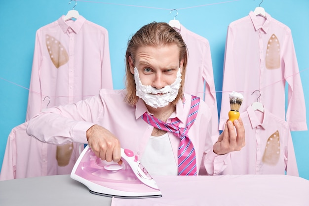 Man kleedt zich aan voor werk strijkt outfit scheert tegelijkertijd wordt laat wakker gekleed in formeel overhemd met stropdas poseert op blauw