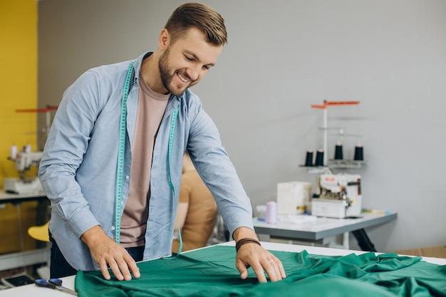 Man kleermaker aan het werk in zijn fabriek