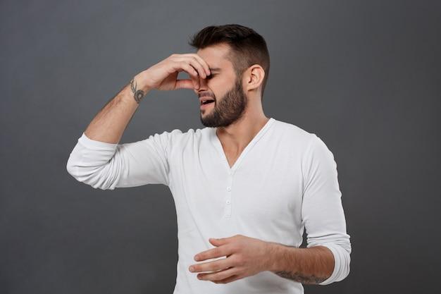 Man knijpt neus vanwege stank over grijze muur